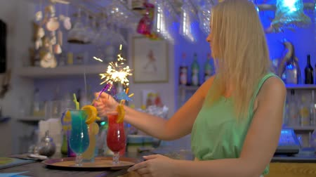 çakmak : Slow motion of a woman setting on the sparklers in cocktails at the bar counter. Party time Stok Video
