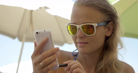 yansıma : Young smiling blond woman using smartphone with a pen on hot summer day, hand and mobile reflecting in sunglasses. Beach parasols in background