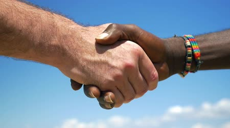 дружба : Slow motion close-up shot of European and African men shaking hands on blue sky background. International or interracial relations and friendship