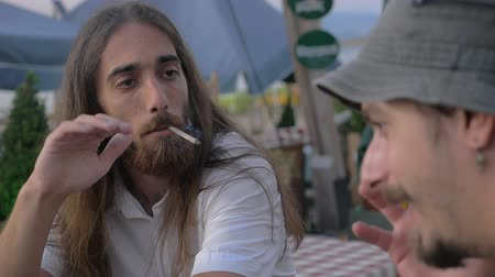 bizonyítani : Slow motion of two male friends sitting in outdoor cafe. They smoking and having a talk. One man is long-haired with beard, another is wearing a bucket hat Stock mozgókép