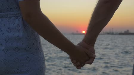 Slow motion steadicam shot of young loving couple holding hands on background of sea and sunset. Affair and romance