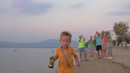 Slow motion steadicam shot of a little boy with medal and cup running along the beach, happy family applauding to his success. First victories