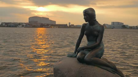 kodaň : Slow motion of rippling water with golden sun reflection and The Little Mermaid statue on the stone in foreground. Copenhagen, Denmark