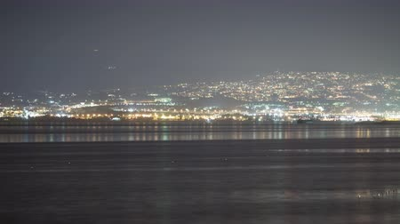 электричество : Timelapse shot of of rippling sea water and distant coastal  city illuminated with electric lights