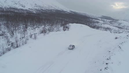 snowfield : Flying over offroader car driving on heavy snowy road. Winter landscape with mountains and bare trees Stock Footage