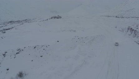 alpy : Aerial view of a car getting through the heavy deep snow on mountain road on dull winter day