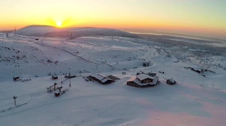 snowfield : Aerial shot of ski resort. View to the area with wooden buildings and ski-lifts. Evening sky in light of golden sunset. Scene with snowfields and hills. Khibins, Russia Stock Footage