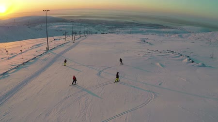 четыре человека : Aerial shot of two skiers and two snowboarders moving down the ski-run at sunset. Snowfields and hills in the distance. Doing winter sports