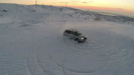 snowfield : Aerial shot of a car drifting on snowfield making circles with view to the distant snow covered hills and evening sky. Beautiful northern nature