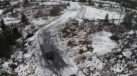 snowfield : Aerial view of minivan driving along snowy rural road in the northern town. Living in severe climate