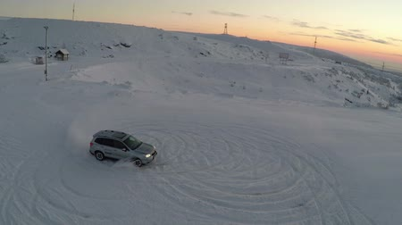 snowfield : Aerial shot of skilled driver making circles on the snow while drifting. Winter nature and evening sky scene