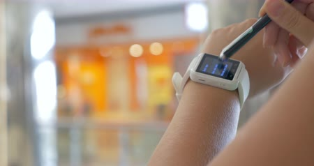 előny : Closeup shot of smart watch on wrist of female user, she is touching the screen with stylus.