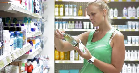 bath salts : Young woman shopping in the store. She taking some cream tubes and bath salts in the beauty care section. Great assortment of body care goods on the shelves Stock Footage