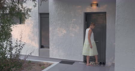 odejít : Young woman leaving home at sunset. She putting on the shoes at the doorstep and walking away. Rent of houses, villas and hotels for holiday
