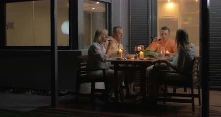 cozy : Close-up of family clinking glasses and eating dinner while sitting on veranda