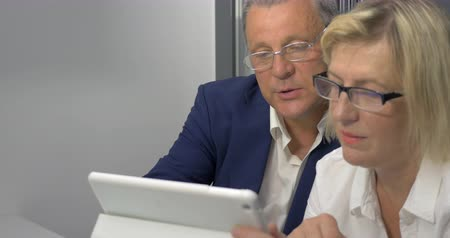 dialog : Senior man and woman in glasses talking on business and using tablet computer. They have positive and constructive conversation
