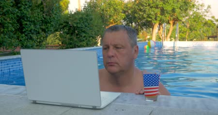 komputer : Senior man working with laptop and having juice not leaving the swimming pool. Doing job on holidays