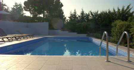 holiday villa : Swimming pool with clear blue water in hotel area or by the villa surrounded by green trees. Empty chaise-longues and tiled floor shining in the sun Stock Footage