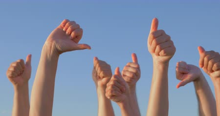 levegő : Group of people is raising hands in the air giving thumbs up and down.