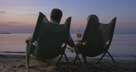 deck chairs : Senior man and woman sitting in chaise longues at the seaside in the evening. They clanging glasses with cocktails and relaxing looking at the sea