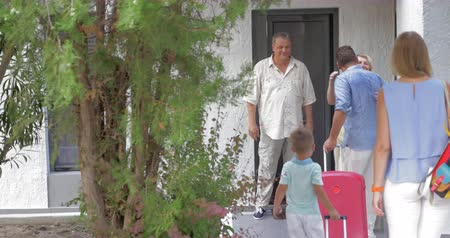 приехать : Young couple with little boy is coming to visit their parent, who are welcoming them at the door.