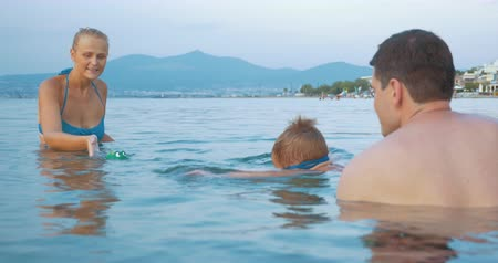 windup : Young parents and little son bathing in the sea. Mom and child playing with windup frog. Family summer vacation Stock Footage