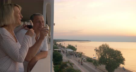 estância turística : Steadicam shot of senior family couple spending evening on drinking wine on hotel balcony on resort. They looking at scenic seascape with sunset Stock Footage