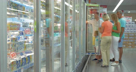 hűtőgép : Family members are standing by the refrigerator in the store, opening the doors and choosing goods. Shot is slightly defocused for adding your content on the foreground. Stock mozgókép