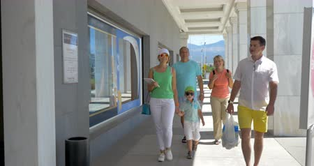 entrance : Parents with son and grandparents walking through the automatic doors of supermarket. Family going shopping together