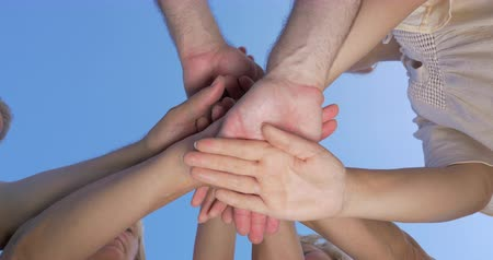 дружба : Bottom shot of young and senior people putting hands together and raising them on blue sky background. Motivation and teamwork Стоковые видеозаписи