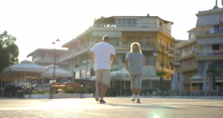 stare miasto : Low angle shot of senior couple at the start of their regular jog. Man and woman running in resort town in bright sunny weather Wideo