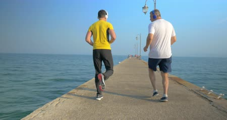 назад : Steadicam shot of senior and young man doing backward exercise on water-front. They run skipping along the pier