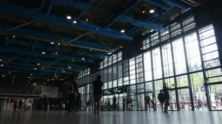 ayrılmak : PARIS, FRANCE - SEPTEMBER 04, 2015: Timelapse shot of stream of people entering and leaving Centre Georges Pompidou. Queue of tourists can be seen outside through the huge windows