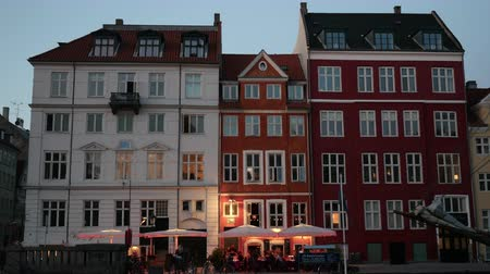 oŚwietlenie : COPENHAGEN, DENMARK- SEPTEMBER 12, 2015: Timelapse shot of of evening coming to the city. View to the classic style building facades in white and red colors with outdoor cafe and parked bikes nearby, people passing by