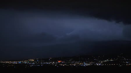 cıvata : Dark sky flashing with lightnings during the night storm over the city
