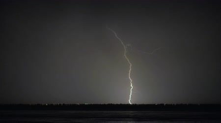 stávka : Night thunderstorm on the coast. Lightning strikes in distant city