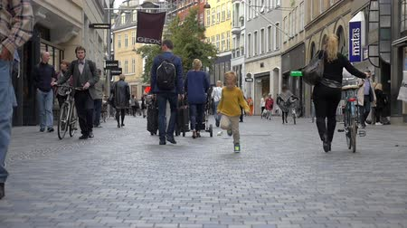 kodaň : COPENHAGEN, DENMARK - SEPTEMBER 15, 2015: Slow motion shot of little boy running along the pedestrian street towards the camera