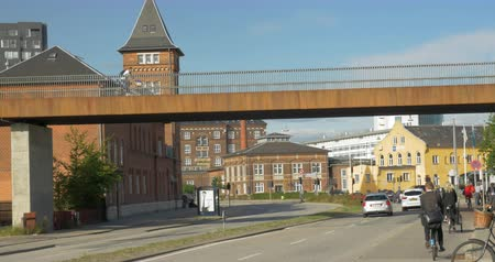 kodaň : COPENHAGEN, DENMARK - SEPTEMBER 10, 2015: City street with bridge over the road. Car traffic and cyclists on the lanes