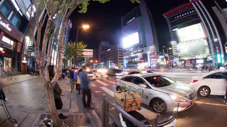 cruzamento : SEOUL, SOUTH KOREA - OCTOBER 22, 2015: Timelapse panning and wide angle shot of busy city street at night. Intense traffic on the motorway and people crossing the road on zebra
