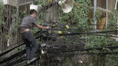 lineman : HANOI, VIETNAM - OCTOBER 27, 2015: Young man electrician doing his job while standing on multiple wires and being saved with belt
