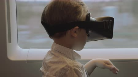 realidade : Little boy traveling by train and entertaining himself with VR-headset. Child exploring virtual space