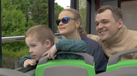 double happiness : Mother, father and son traveling on upper deck of double-decker bus and looking out open window Stock Footage