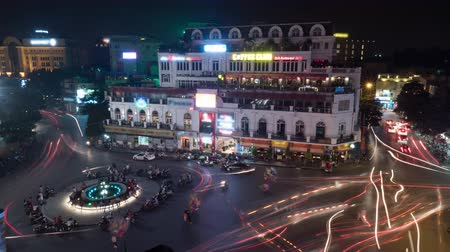 Вьетнам : Timelapse high angle shot of road traffic at night. Illuminated fountain with bikes on the city square and transport moving around it. Hanoi, Vietnam