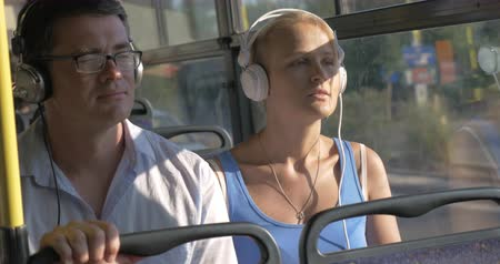 fone de ouvido : Young beautiful couple blond woman and man in glasses listening music in headset during bus trip against bus windows view Vídeos