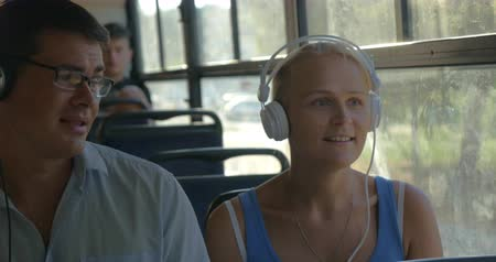 fone de ouvido : Young couple listening to music on headphones during the bus ride. They dance to the music, man singing