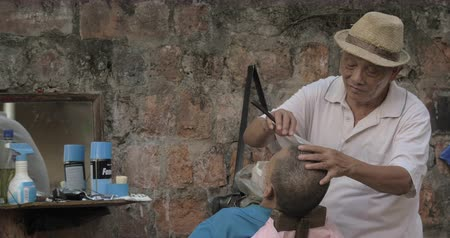 shaves : HANOI, VIETNAM - OCTOBER, 20, 2015: Senior man shaving another man by old blade on stone wall background, traditional haircut. Hanoi is a very picturesque city, popular tourist attraction Stock Footage
