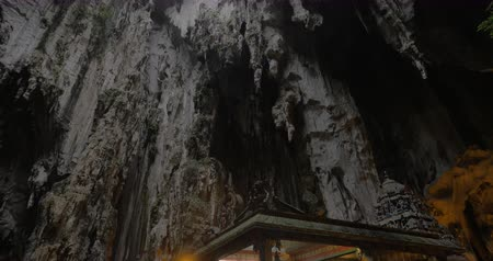 východní : KUALA LUMPUR, MALAYSIA - NOVEMBER 5, 2015: In Batu Caves seen cave with stalactite and walking tourists near the sacred temple. Malaysia is visited by more than 25 million turists annually