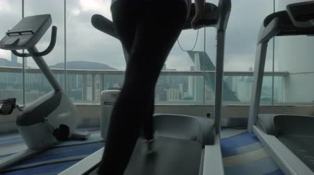hong kong foot : Close up view of young blond woman jogging on the treadmill in fitness centre looking at window with modern building cityscape from different side of view. Hong Kong, China