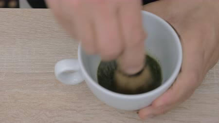 puder : Close-up shot of making matcha tea. Pouring some water into cup with green powder and mixing with whisk