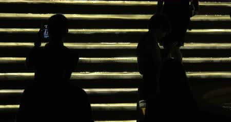 oŚwietlenie : Silhouettes of people going up and down and taking picture by smartphones on lighting gold stairway. Bangkok, Thailand Wideo